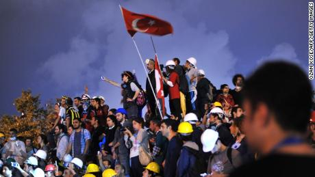 Anti-goverment protesters unfurl the Turkish national flag in Gezi Park in June 2013.