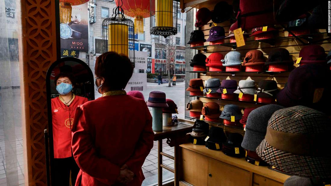 "A sales clerk wears a mask as she waits for customers at a hat shop in Beijing on February 18.<a href=""https://www.cnn.com/2020/02/14/economy/coronavirus-china-economy-small-businesses/index.html"" target=""_blank""> </a>Small companies that help drive China's economy <a href=""https://www.cnn.com/2020/02/14/economy/coronavirus-china-economy-small-businesses/index.html"" target=""_blank"">are worried about how much damage</a> the coronavirus outbreak will cause to business."