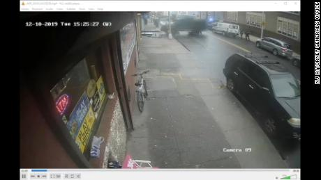 The surveillance video shows a police vehicle driving into the supermarket shop and dragging building debris with it.