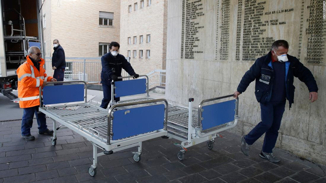 Hospital personnel in Codogno, Italy, carry new beds inside the hospital on February 21. The hospital is hosting some people who have been diagnosed with the novel coronavirus.