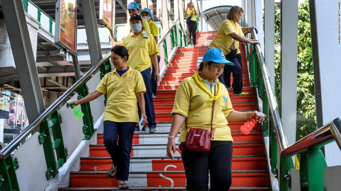 A team of volunteers disinfects a pedestrian bridge in Bangkok, Thailand.