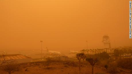 Planes are pictured at Tenerife SouthReina Sofia Airport during a sandstorm on February 23, 2020 on the Canary Island of Tenerife. - Airports on Spain's Canary Islands were closed after strong winds carrying red sand from the Sahara shrouded the tourist hotspot.