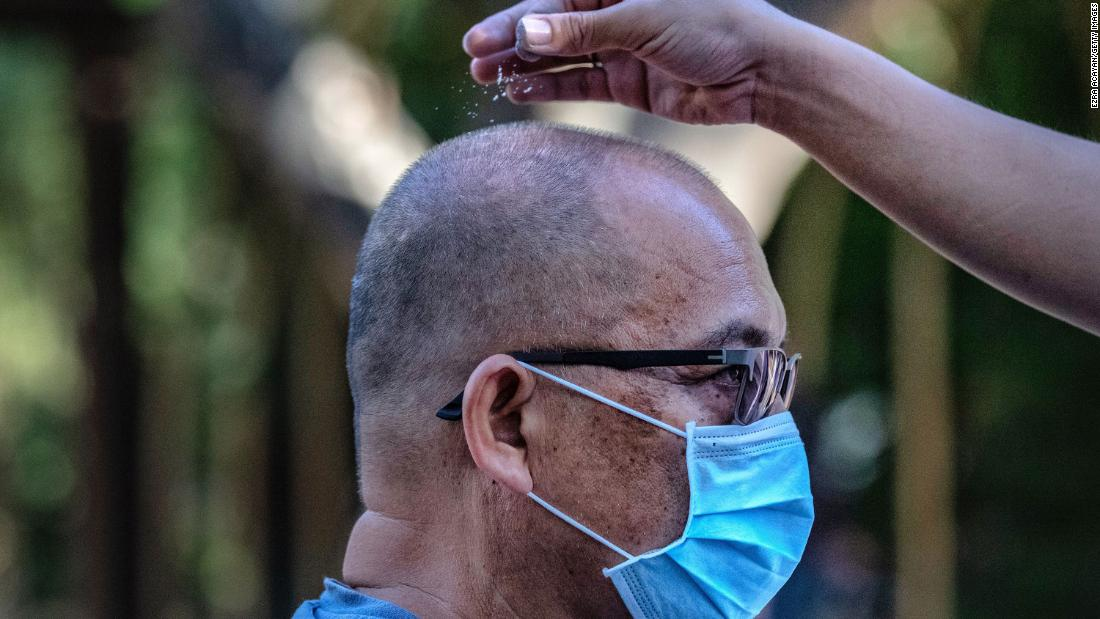 A Catholic devotee wears a face mask as he is sprinkled with ash during Ash Wednesday services in Paranaque, Philippines, on February 26.