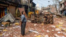 A resident looks at burnt-out and damaged residential premises and shops following clashes on Tuesday.