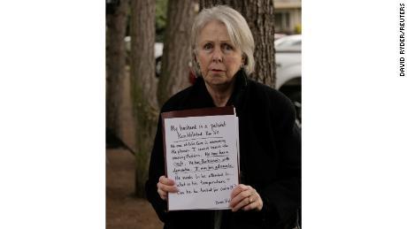 Bonnie Holstad holds a sign explaining concern for her husband, Ken.
