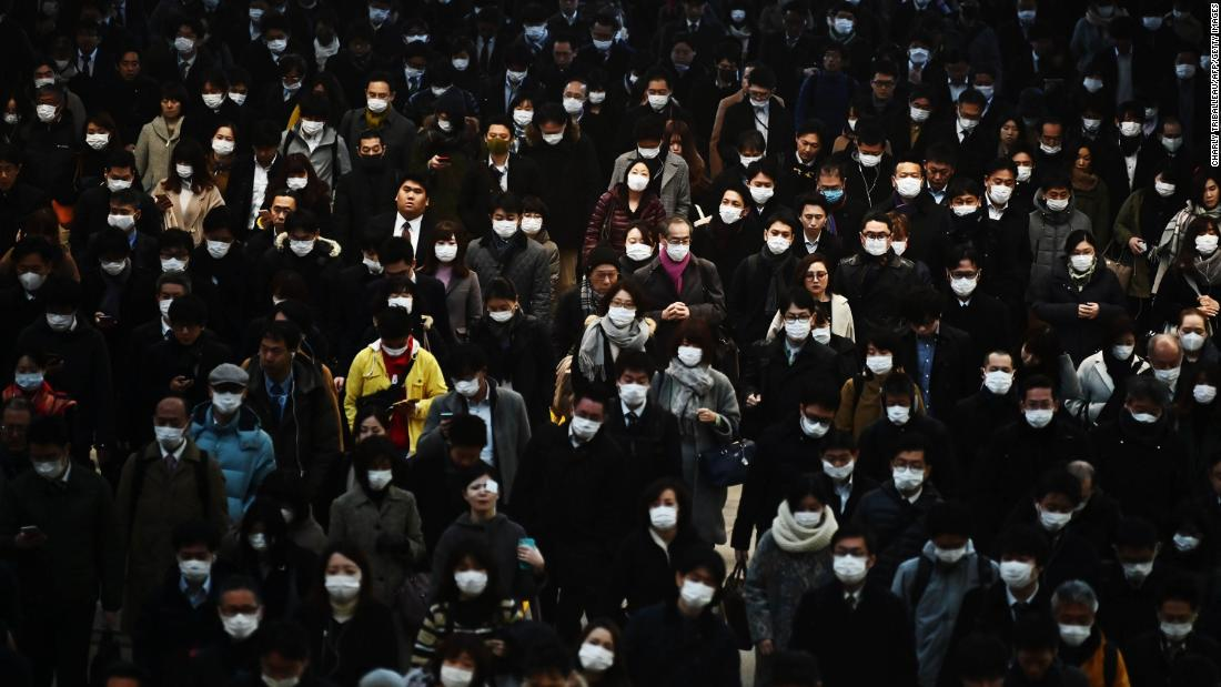 Commuters wearing masks make their way to work during morning rush hour at the Shinagawa train station in Tokyo on February 28.