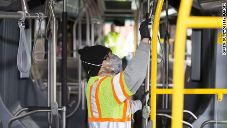 A Seattle transit worker deep cleans a bus.
