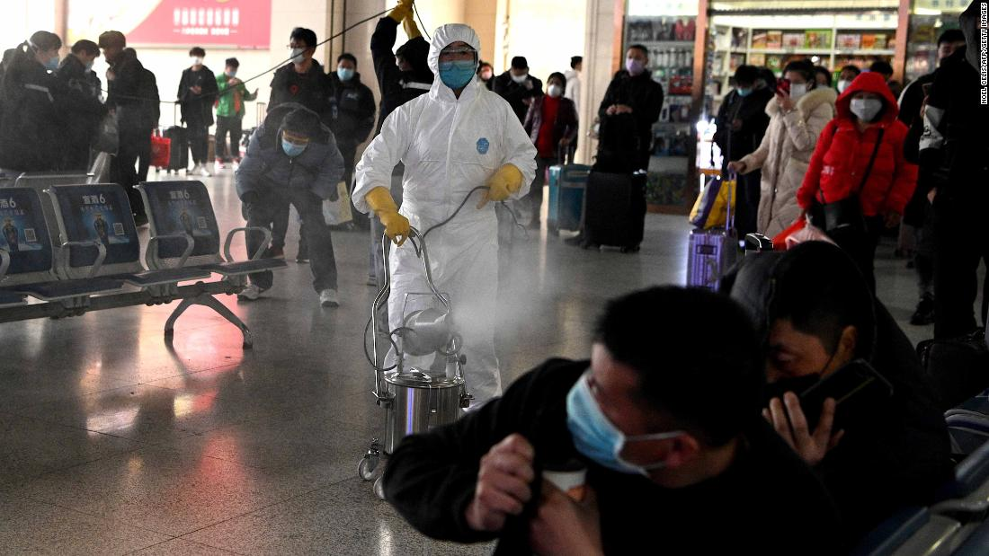 Passengers react as a worker wearing a protective suit disinfects the departure area of a railway station in Hefei, China, on March 4.