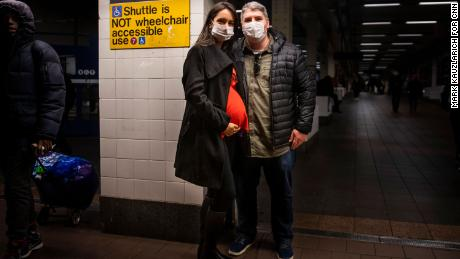 Leonardo Gayer and wife Vanessa, visiting from Brazil, wear surgical masks in the New York subway.