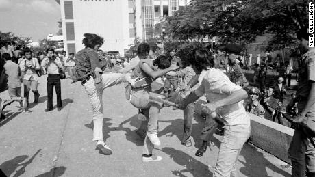 In this Oct. 6, 1976 file photo right-wing Thai students kick and beat a leftist student who surrendered after a battle on the campus of Thammasat  University in Bangkok, Thailand.