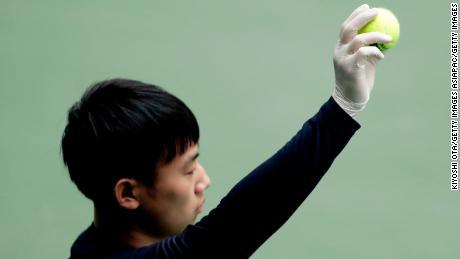 A ball boy wears a rubber glove as a preventive measure against the novel coronavirus.