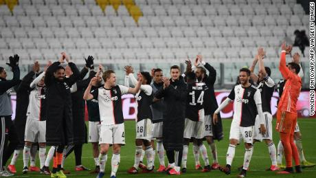 Juventus players applaud the empty stands after their win.