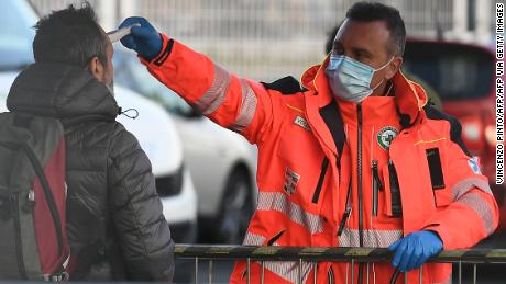 A health staff checks the body temperature of a man arriving at the stadium.
