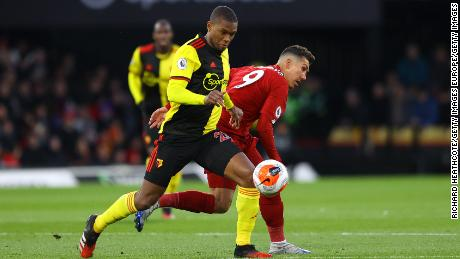 Kabasele battles for possession with Liverpool's Roberto Firmino.