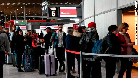 Travellers queue at an airport information desk at Paris-Charles-de-Gaulle airport after a US 30-day ban on travel from Europe.