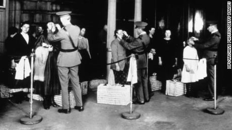 Immigrants being inspected at Ellis Island, New York, in the early 1900s for signs of disease as they arrive in the United States.