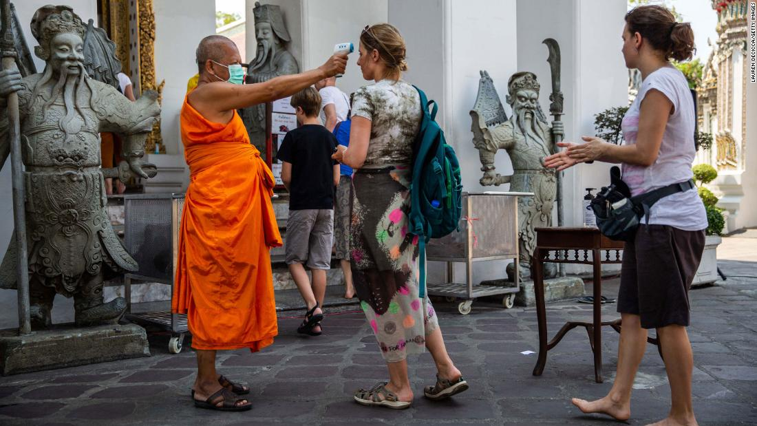 Body temperatures are scanned as people enter the Buddhist temple Wat Pho in Bangkok, Thailand, on March 13.