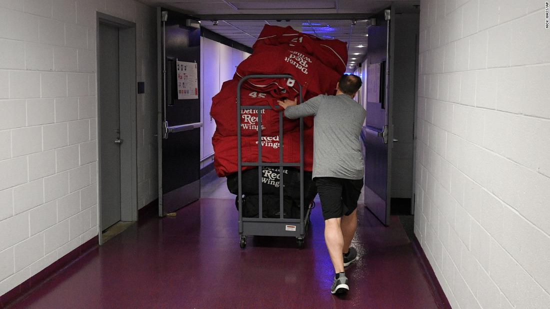Paul Boyer, head equipment manager of the NHL's Detroit Red Wings, wheels out equipment bags in Washington on March 12. The NHL is among the sports leagues that have suspended their seasons.