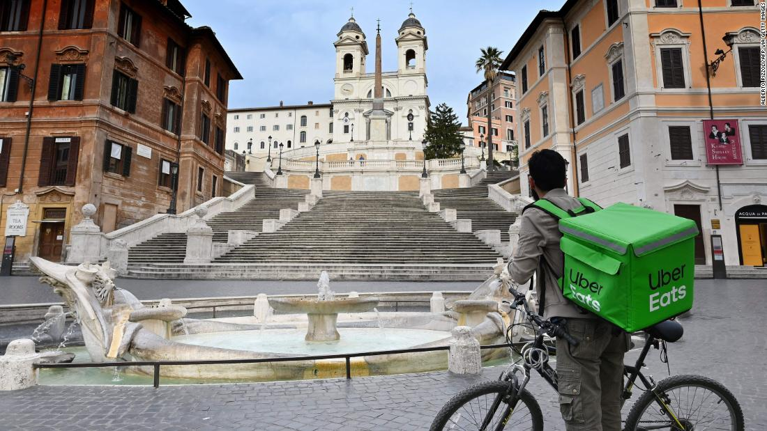 An Uber Eats delivery biker stands at a deserted Piazza di Spagna in Rome.