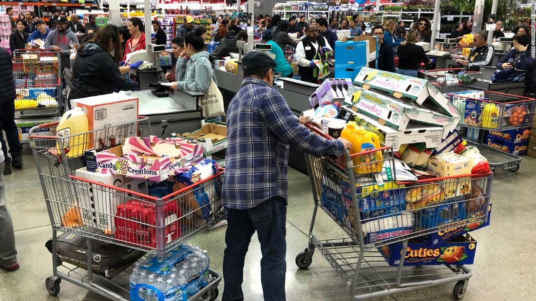 A Costco customer stands by two shopping carts in Richmond, California, on March 13.