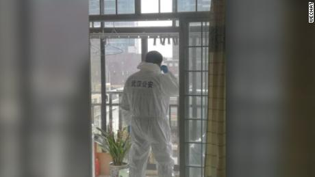 A photo on Wechat shows a local policeman in protective suit stationed on a balcony to discourage any potential yelling or jeers from residents.