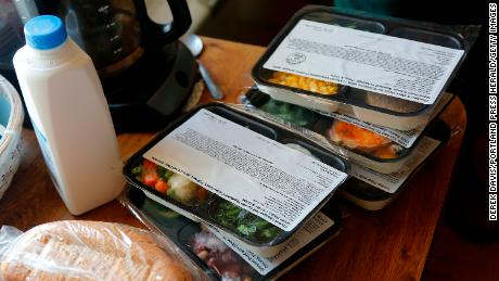 Volunteers at Meals on Wheels deliver food to a man in Portland.