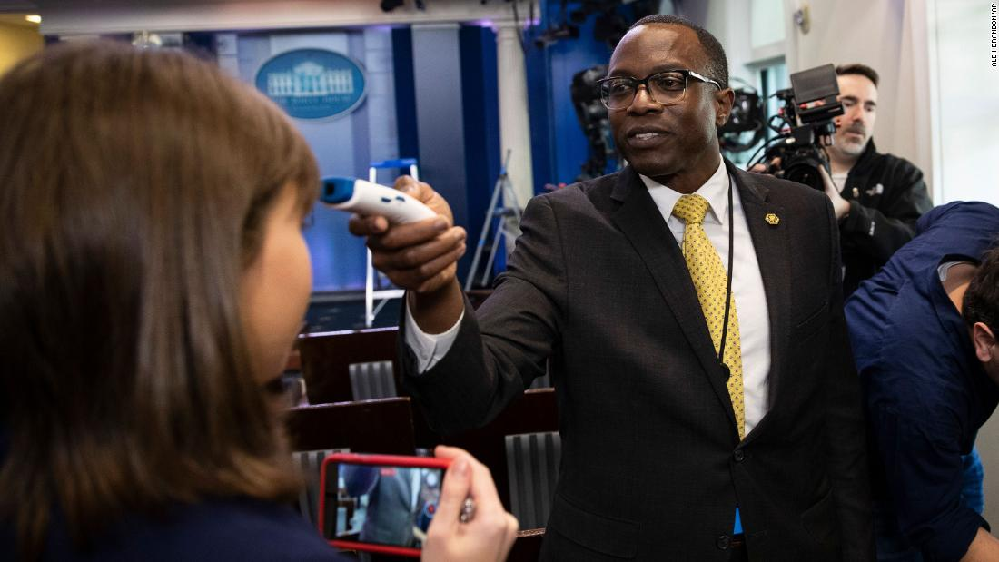 A member of the White House physician's office takes a media member's temperature in the White House briefing room on March 14. It was ahead of a news conference with President Donald Trump and Vice President Mike Pence.