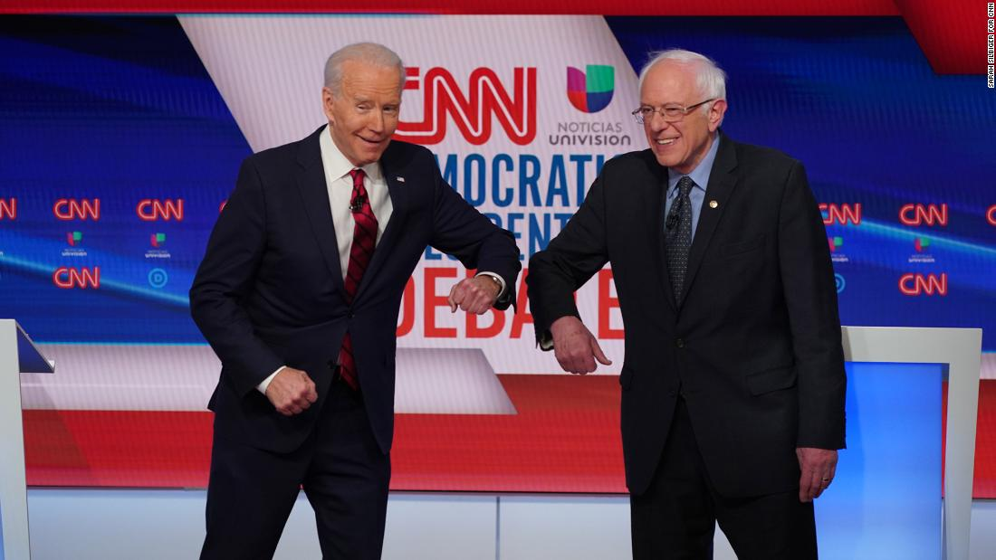 "Biden greets US Sen. Bernie Sanders with an elbow bump before the start of <a href=""http://www.cnn.com/2020/03/15/politics/gallery/debate-washington-biden-sanders/index.html"" target=""_blank"">their one-on-one debate</a> in Washington, DC, in March 2020. The two Democrats went with an elbow bump instead of a handshake because of the coronavirus pandemic. Sanders ended his presidential campaign the following month, clearing Biden's path to the Democratic nomination."