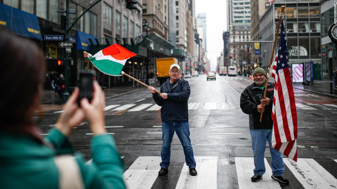 "Dermot Hickey, left, and Phillip Vega ask a pedestrian in New York to take their picture on a thinly trafficked Fifth Avenue on March 17. Many streets across the world are much more bare as people distance themselves from others. In the United States, the White House advised people <a href=""https://www.cnn.com/2020/03/16/politics/white-house-guidelines-coronavirus/index.html"" target=""_blank"">not to gather in groups of more than 10.</a>"