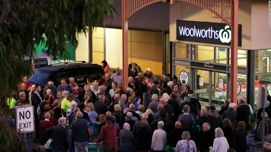 People wait outside a Woolworths store in Sunbury, Australia on March 17. Australian supermarket chains announced special shopping hours for the elderly and people with disabilities so that they can shop in less crowded aisles.