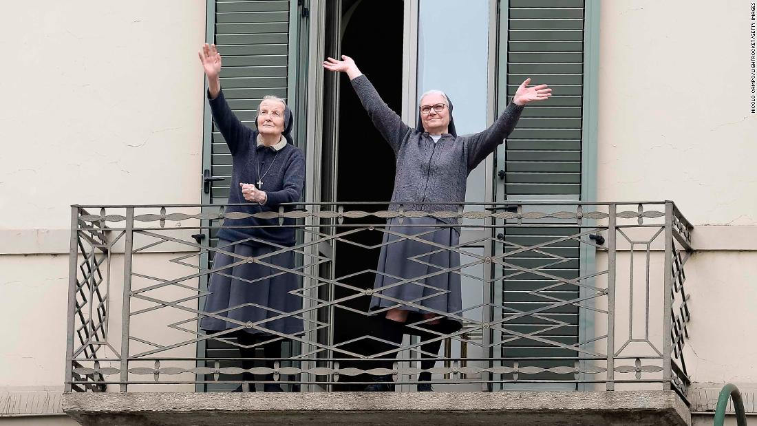 Two nuns greet neighbors from their balcony in Turin, Italy, on Sunday, March 15.