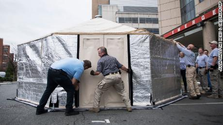 Members of the State Medical Assistance Team assemble a triage tent outside UNC Health's emergency department in Chapel Hill, North Carolina, to reduce pressure on the facility.