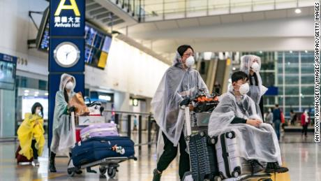 Travellers wearing protective equipment enter the arrival hall at the Hong Kong International Airport on March 17, 2020 in Hong Kong.