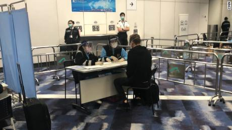 Quarantine officers interview Will Ripley on arrival at  Hong Kong International Airport on March 15.