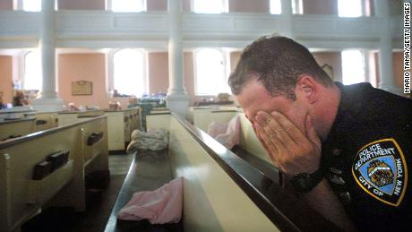 An NYPD officer rubbed his eyes after snapping on a pew at St. Paul's Chapel near the site of the World Trade Center attack in 2001.