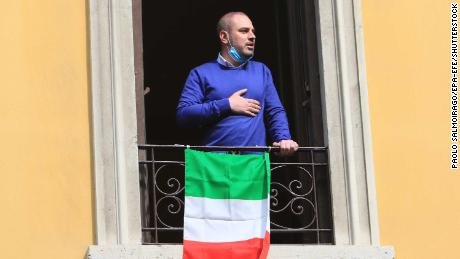 A resident appears at his window, singing the national anthem.