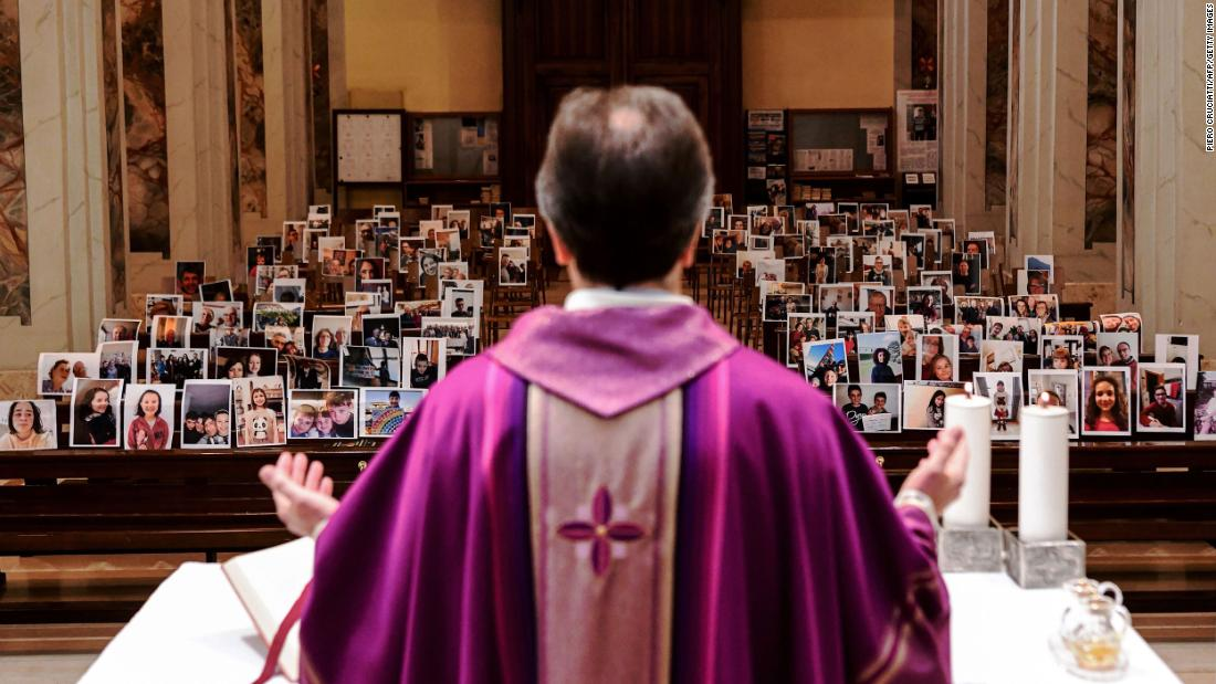 Giuseppe Corbari holds Sunday Mass in front of photographs sent in by his congregation members in Giussano, Italia, a marzo 22. Many religious services are being streamed online so that people can worship while still maintaining their distance from others.