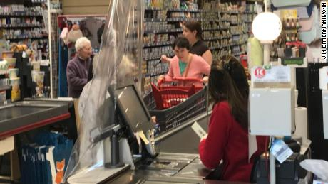Cashiers separated from customers by plastic.