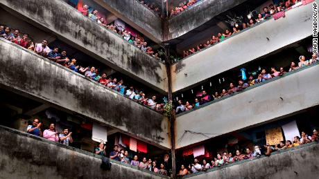 People clap from balconies in show of appreciation to health care workers in Mumbai, India on March 22, 2020.