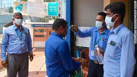Security personnel wear face masks as they check the temperature of visitors to a hospital in Bangalore on March 16, 2020.