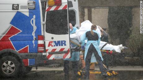 A patient is shielded while being put into an ambulance outside the Life Care Center of Kirkland on March 7, 2020.