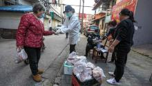 People buy pork at the gate of a closed residential community in Wuhan on March 18.