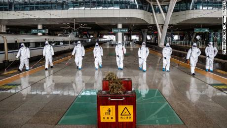 Staff members spray disinfectant at the Wuhan Railway Station on March 24.