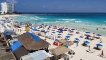 People enjoy a day at the beach in Cancun, Mexico, over the weekend, despite the coronavirus pandemic.