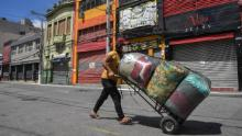 A street vendor walks along an empty popular shopping street in downtown Sao Paulo during its lockdown.