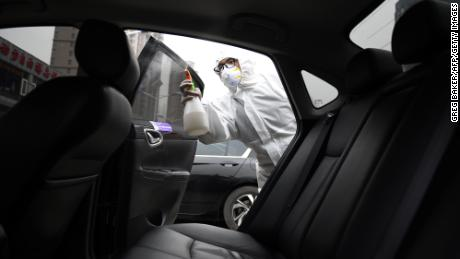A worker wears protective clothing as he disinfects a car for Chinese ride hailing company Didi in Beijing in February.