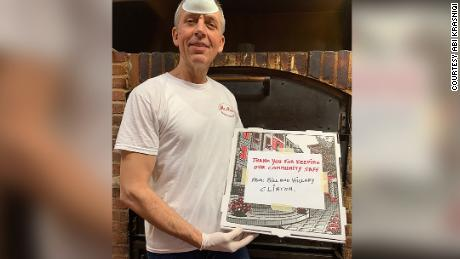 Nick Krasniqi of Mr. Nick's Brick Oven Pizza standing with one of the pizzas that were delivered to Phelps Memorial Hospital.