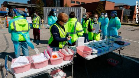 Health care workers prepare their supplies Wednesday at a coronavirus drive-thru testing site at Michigan's Henry Ford West Bloomfield Hospital.