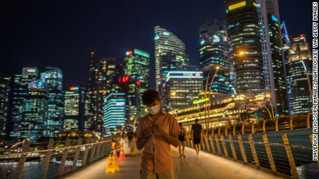 SINGAPORE - 2020/02/12: A man wearing protective surgical masks walks along the Merlion Park, a major tourist attraction in Singapore. Singapore declared the Coronavirus outbreak alert as Code Orange on February 7, 2020. (Photo by Maverick Asio/SOPA Images/LightRocket via Getty Images)