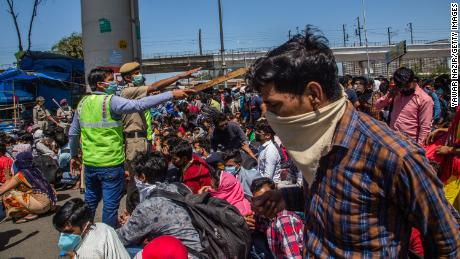 Indian migrant workers stuck in the national capital try to board buses to return to their home villages.
